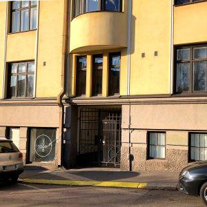 En gul fasad med en brun stålport och två parkerade bilar framför.