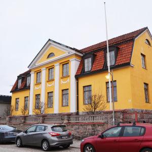 På bilden syns ett stort gult hus med vita detaljer.