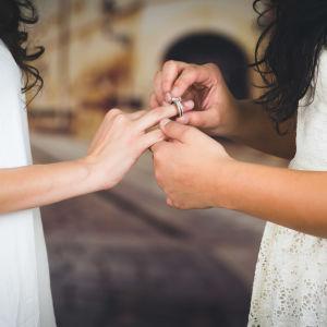 En kvinna i bröllopsklänning sätter en ring på fingret på en annan kvinna i bröllopsklänning.