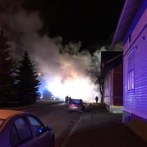 Puutaloalueella näkyy palon savua ja savun takana vähän liekkejä.