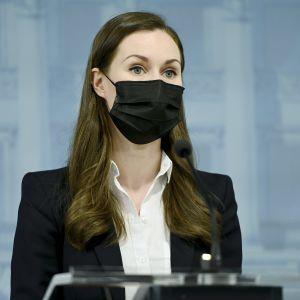 Sanna Marin på presskonferensen i munskydd.
