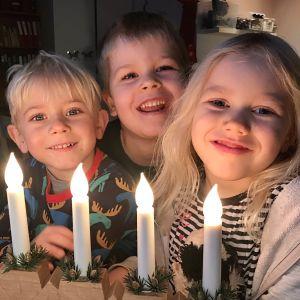 Tre barn i dagisåldern vid elljusstake.