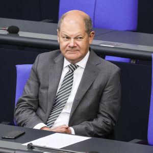 Olaf Scholz istuu.