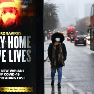 Terveysilmoitus muistuttaa pysyttelemään kotona Lontoossa sijaitsevan bussipysäkin kupeessä. Ilmoituksessa korostetaan, että koronan uusi variantti leviää hyvin nopeasti.
