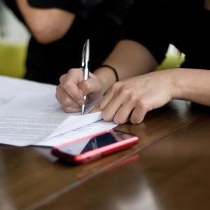Personer skriver på ett papper.