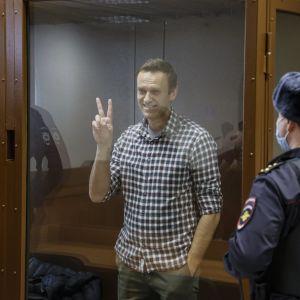 Den ryska oppositionsledaren Aleksej Navalnyj visar segertecknet i rätten