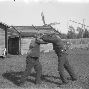 """Två män leker """"kragtag"""", där man håller i sin motståndares krage och försöker fälla denna på rygg. Bilden är tagen 1930 i Korsnäs kyrkby."""