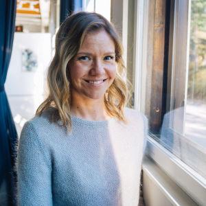 Sonja Kailassaari står vid ett fönster där ljuset strömmar in.