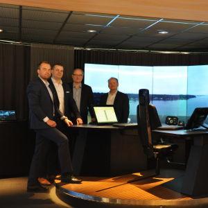 Fyra herrar står kring bordet vid Kongsbergs fartygssimulator, som föreställer ett bord från vilket man kan fjärrstyra ett fartyg.