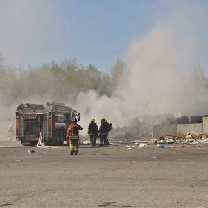 Fyra brandmän med utrustning står bredvid en brandbil med slangarna ute. Framför dem ryker det kraftigt.