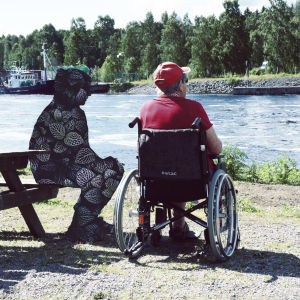 En vårdare och en man i rullstol tittar ut över floden