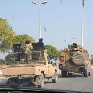 Två militärfordon på en asfalterad väg i Syrien.