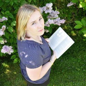 Lukuhumua kirjablogin kirjoittaja Joanna von Scarlett kirjan kanssa puutarhassa