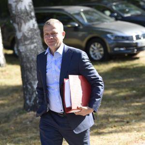 Petteri Orpo kommer gående i solskenet iklädd blå kostym med en röd pärm under armen och ett vagt leende på läpparna.