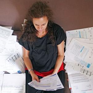 Nainen istuu asiakirjojen ympäröimänä.