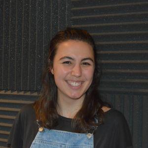 En leende brunhårig kvinna framför en brun vägg.