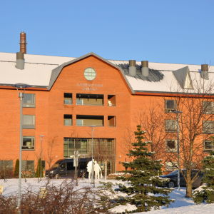 Stor rödbrun tegelbyggnad i solljus.