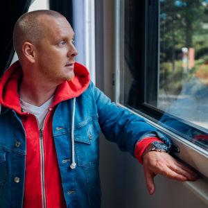 Lasse Mellberg tittar ut från fönster.