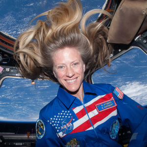 Astronautti Karen Nyberg katsoo kameraan hymyillen avaruussukkulassa, jonka ikkunoista näkyy maapallo.