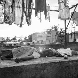 två flickor ligger på en stenplatta på en takterass