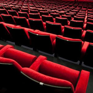 Röda stolar i en teater- eller biosalong.