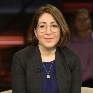 Deborah Feldman i brun page, stora glasögon med tunna bågar. Bruna ögon, svart kavaj och ett guldhalsband. Porträttfotografi.