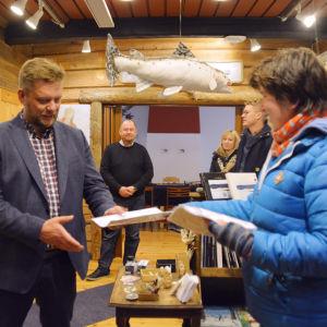 Henrik Jansson tar emot en bunt papper av Jonna Engström-Öst i Ekenäs naturum.