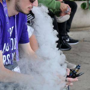 En e-cigarettrökande man sitter på en bänk och blåser ut ånga.