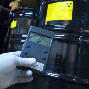 En geigermätare och tunnor med radioaktivt material i bakgrunden.