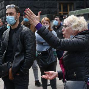 En kvinna gestikulerar under en demonstration mot coronarestriktionerna i Ukraina