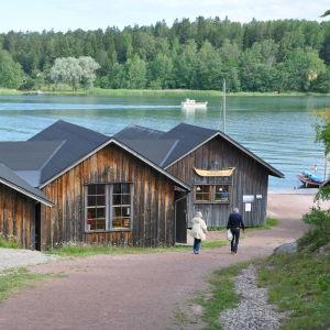 I förgrunden båtmuseet i Näsby med sina låga hus, i bakgrunden den blå Hålaxviken.