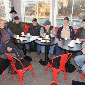 8 män sitter på café