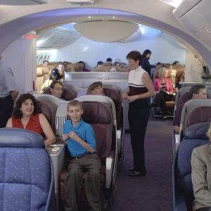 Boeing 787 Dreamliner -lentokoneen mallimatkustamo, jossa on ihmisiä ja henkilökuntaa.