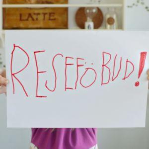 """Ett barn håller upp ett stort pappersark med texten """"RESEFÖBUD!""""."""
