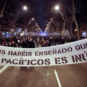 """""""Olette opettaneet meille, että rauhanomaisuus hyödytöntä"""", lukee mielenosoittajien Barcelonassa sunnuntaina kannattelemassa banderollissa."""