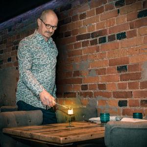Jyrki haluttunen sytyttää kynttilää Ravintola Harmoonissa.