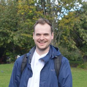 Man i blå jacka och ryggsäck ler stort mot kameran. I bakgrunden syns träd.