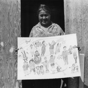 Nainen pitelee kädessään piirtämäänsä kuvaa. Kuvassa on ihmisiä.