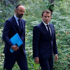 Edouard Philippe och Emmanuel Macron går sida vid sida ute i en trädgård. 29.6.2020