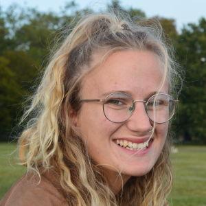 Kvinna med ljust, lockigt hår och glasögon ler stort in i kameran.