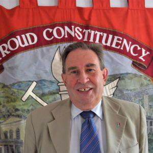 En man står och ler framför en röd flagga.