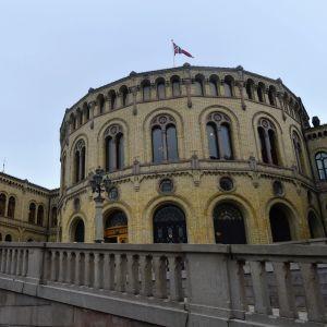 Parlamenttirakennus. Katolla liehuu Norjan lippu.