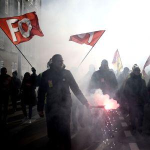 Demonstranter med röda flaggor med bokstäverna FO i vit text. Det är flera människor på rad och bilden är mörk och det är rökigt.