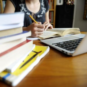 En kvinna sitter vid ett köksbord med en boktrave och en laptop framför sig.