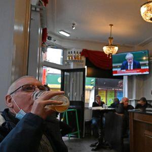 En man sitter på en pub i Liverpool och dricker ur ett stort ölglas.
