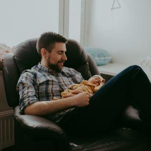Jim håller i sin nyfödda son i famnen på sjukhuset.