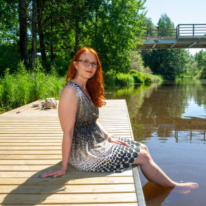 Työterveyspsykologi Mari Laari istuu Kerava-joen laiturilla.