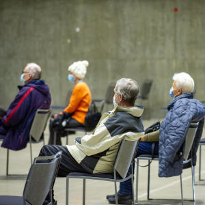 Äldre personer i munskydd väntar på coronavaccin i Borgå i mars 2021.