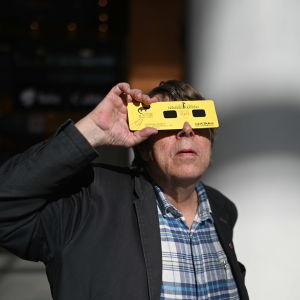 Mikkeliläinen Raimo Laitinen kuvattu Mikkelin Stellassa hänen suunnittelemat auringonpimennyslasit silmillään.