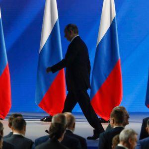I bakgrunden flera ryska flaggor, framför den en kostymklädd man som går och i förgrunden huvuden tillhörande en publik.  Rysslands president Vladimir Putin lämnar podiet efter sitt tal till nationen den 15 januari 2020.